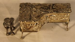 A miniature silver piano and stool