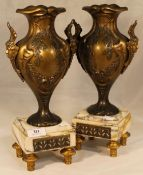 A pair of marble base figural urns