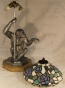 A lamp in the form of a monkey with a stained glass shade