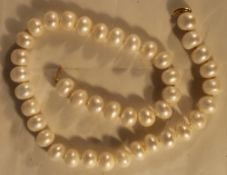 A string of pearls with a 14 ct gold clasp