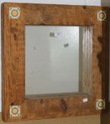 A tile inset wooden framed mirror