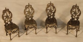 A miniature silver set of four chairs