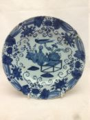 An antique blue and white Delft plate, decorated with vases issuing flowers in the Chinese style.