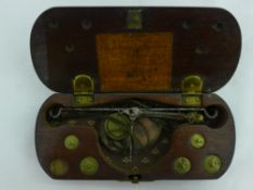 A cased set of miniature scales and weights
