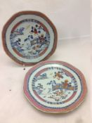 A pair of Chinese porcelain plates, each centrally decorated with a fenced garden river landscape.