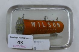 A glass advertising paper weight for Wilson,