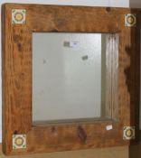 A tile inset wooden framed mirror