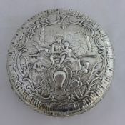 An embossed round silver box