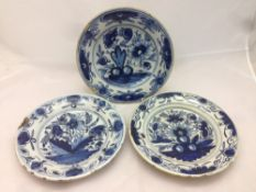 Three antique blue and white Delft plates, each decorated with floral sprays,
