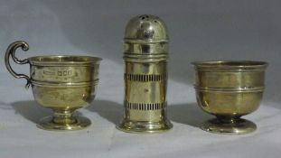 Two silver egg cups and a silver pepper