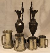 A pair of pewter ewers and plated tankards