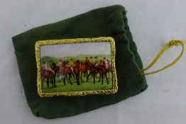 An 18 ct gold plated snuff box, the hinged cover decorated with a horse racing scene. 5 cm wide.