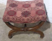 An upholstered X-frame stool