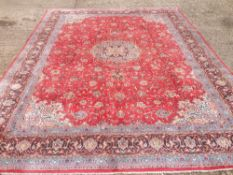 A Sarough wool carpet The wine red field enclosing a central medallion with pendant palmettes