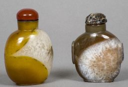Two Chinese carved mineral snuff bottles and stoppers One stopper carved. The larger 8 cm high.