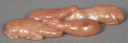 A carved hardstone, possibly rhodonite, animalier group Formed as four sleeping piglets. 8 cm wide.