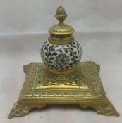 A Victorian brass mounted pottery inkwell The spherical body worked with floral strapwork.
