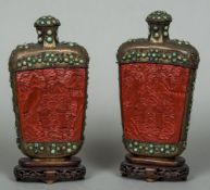 A pair of Chinese cabochon inset metal mounted cinnabar lacquered table snuff bottles Each