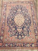 A Persian wool rug The midnight blue field enclosing a central medallion with pendant palmettes