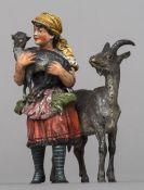 A cold painted bronze figural group Formed as a goatherdess carrying a baby goat,