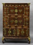 A late 19th century brass mounted Chinese elm cabinet The panelled top above four small drawers