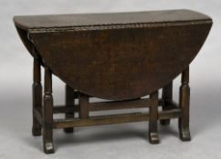 An 18th century oak gateleg table The twin flap oval top above a single frieze drawer,