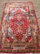 A Hamadan wool rug The wine red field enclosing a pole medallion within rosette spandrels and