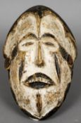 A carved softwood tribal mask With open eyes and mouth and with painted decorations. 28.5 cm high.