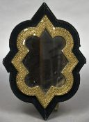 A Victorian gilt wall glass Of Islamic inspired shape, with a plush lined backing plate,