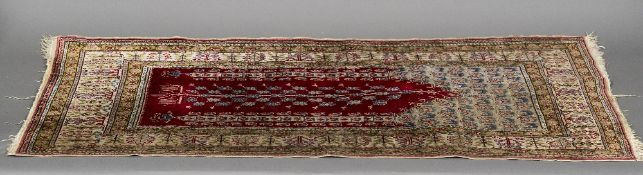 A Persian silk prayer rug With central tree of life flanked by twin obelisks. 112 cm long.