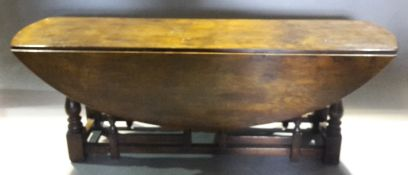 A large 20th century oak twin gateleg drop-leaf dining table The oval hinged plank top above turned