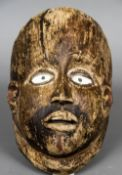 A softwood tribal mask Set with glass eyes and traces of original paint. 30 cm high.