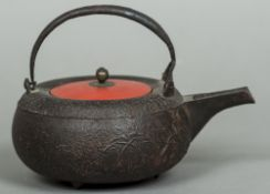 A Japanese cast iron teapot Cast with foliate sprays, the cover red lacquered. 15 cm high overall.