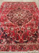 A Bakhtiar wool carpet The wine red field enclosing a central medallion with pendant palmettes