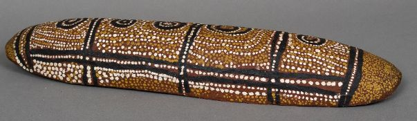 An Australian Aboriginal shield Of domed oval form with typical painted decorations. 73 cm long.