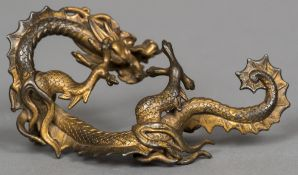 A 19th century Chinese gilt bronze brush rest Formed as a scrolling dragon. 16.5 cm wide.