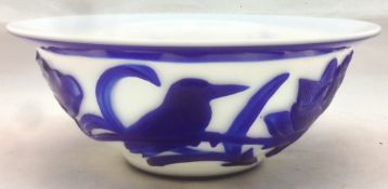 A Chinese Peking glass bowl Blue overlaid on white carved with a bird amongst lotus blossom. 15.