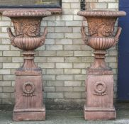 A pair of decorative terracotta garden urns on stands Each of classical form. Each 129 cm high.