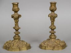A pair of cast bronze candlesticks Worked with C-scrolls and floral sprays,