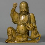 An 18th century Chinese carved butterscotch soapstone figure of a Lohan and Qilin With polychrome