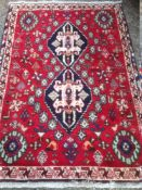 A Caucasian wool rug The wine red field enclosing a central pole medallion within rosettes,