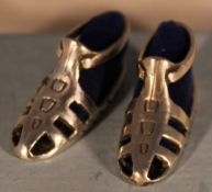 A pair of miniature silver shoes