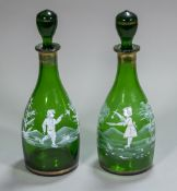 A pair of Victorian Mary Gregory green glass decanters and stoppers Each of mallet form and