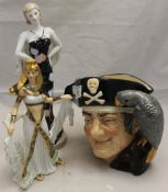 Two Art Deco style porcelain figures and a Royal Doulton long john silver character jug