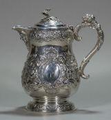 An Edwardian Irish silver embossed lidded jug, hallmarked Dublin 1907,