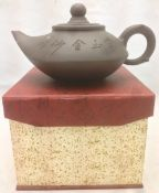 A Chinese Yixing pottery teapot and cover The body with incised decoration and calligraphic script,