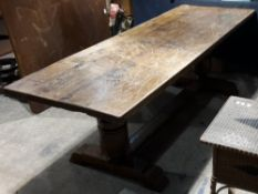 A large oak refectory table The rectangular plank top above twin turned supports,