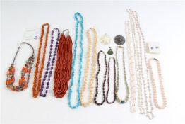 Diverse sieraden, voornamelijk colliers gemaakt van halfedelstenen en een barnstenen collier met