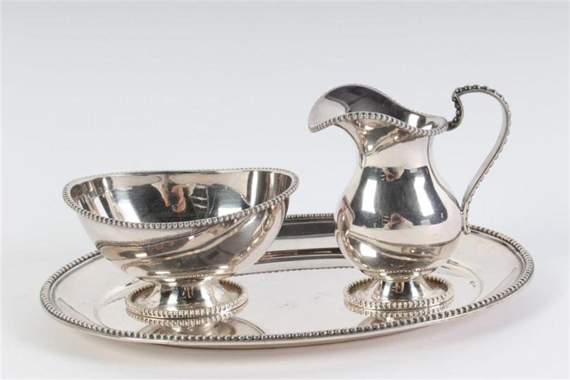 Driedelig zilveren roomsetje met parelrand. L: 18.5 cm. Gewicht: 293 g.