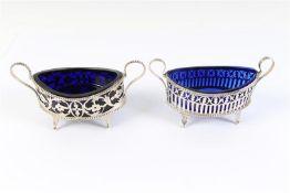 Twee zilveren zoutvaatjes, ajour met parelrand en blauw glazen binnenbak.